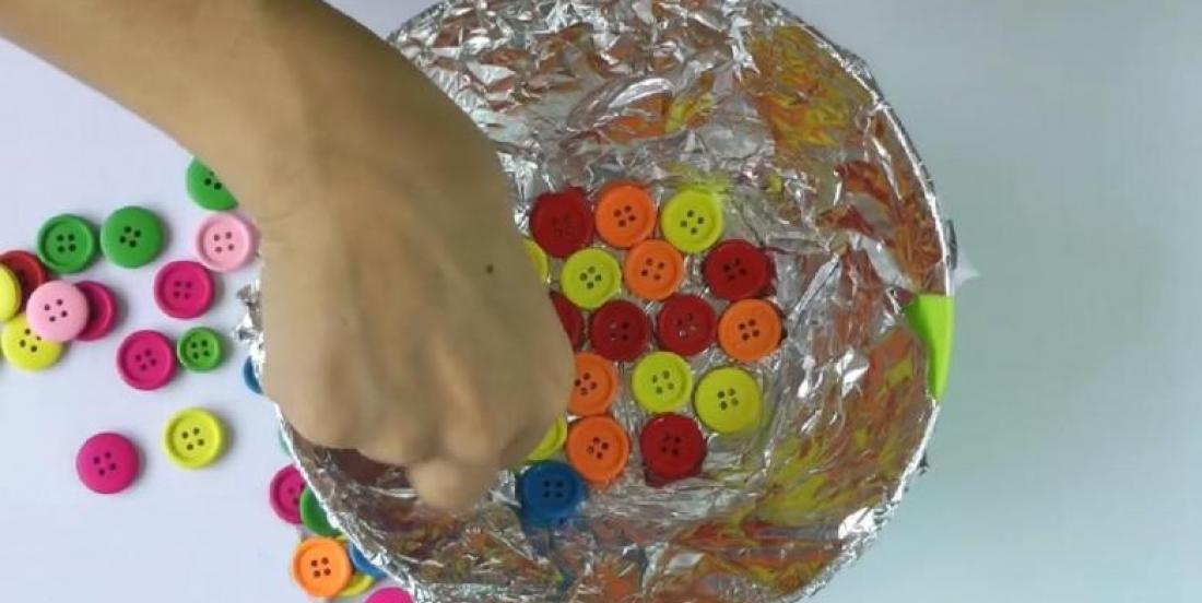Elle colle des boutons sur du papier aluminium! Son bricolage est adorable!
