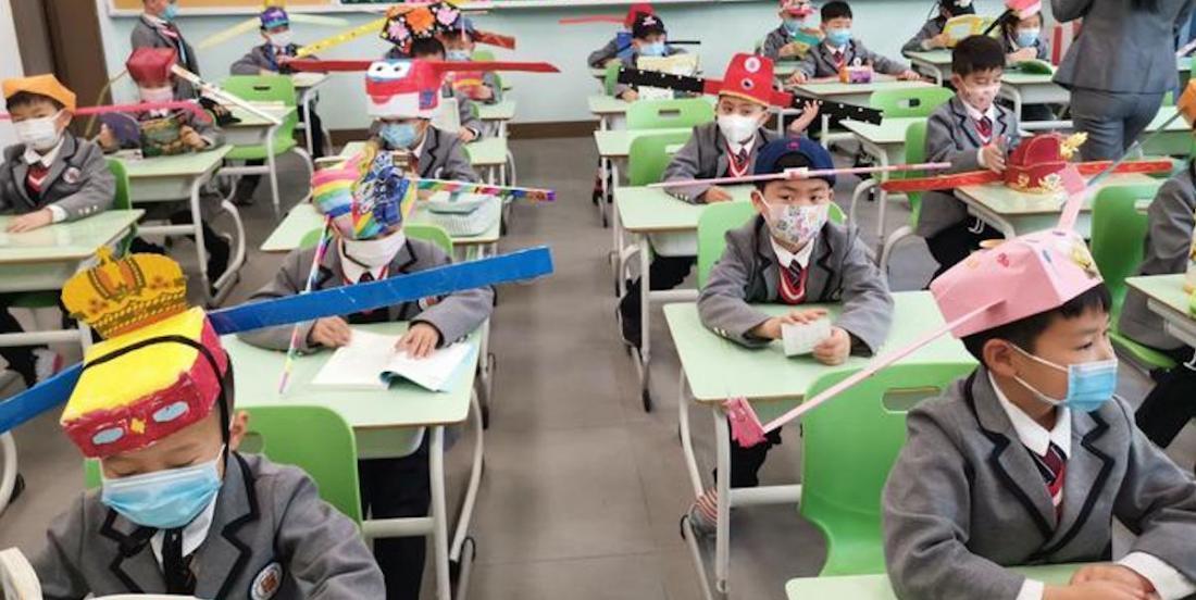 Déconfinement: des enfants chinois retournent à l'école en portant des chapeaux de distanciation sociale