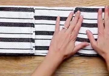 Avec une simple serviette, elle réalise une accessoire de cuisine qu'on voudra tous dorénavant!!