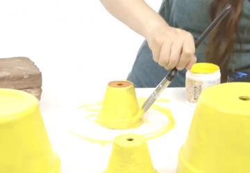Après avoir peint 4 pots de fleurs en jaune, elle réalise la plus mignonne des décorations pour le jardin!