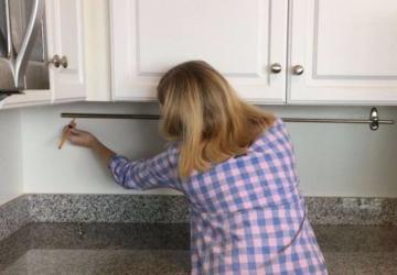 En installant une tringle à rideaux sur son mur de cuisine, elle ajoute un rangement auquel on ne penserait pas!