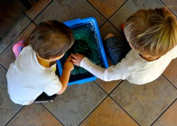 Maman ajoute de l'eau coloré dans un grand bac en plastique et le congèle! Les enfants passent des heures à jouer avec son idée!