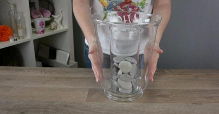 Elle met un vase dans un autre et elle ajoute des cailloux. Quand elle verse de l'eau, la magie opère!