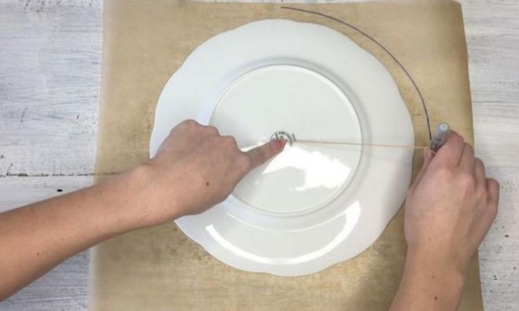 Elle place une assiette sur du papier et trace un grand cercle: son idée de napperon est vraiment inusitée!