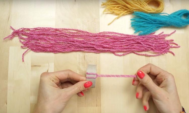 Elle coupe plusieurs bouts de laine et les enfile sur un rouleau. Quand elle finit, c'est complètement adorable!